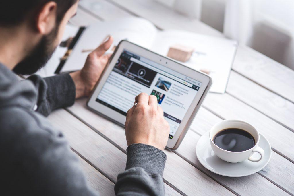 Mann liest einen Artikel auf einem Tablet