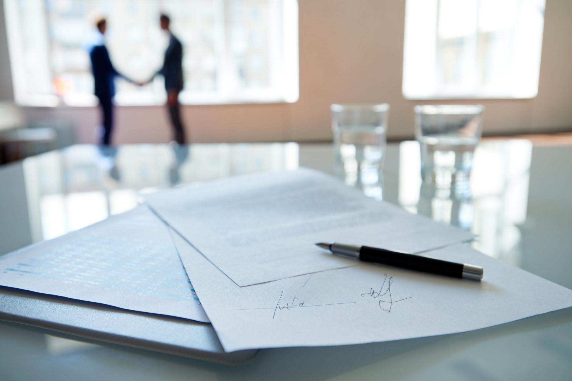 Signed business contract lying on table, business partners shaking hands in the background