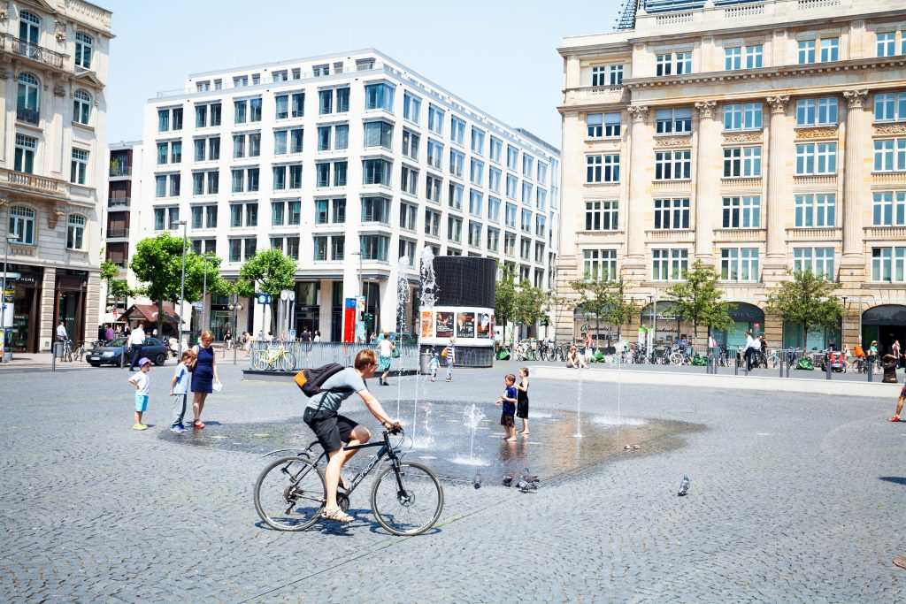 Frankfurt Main, Germany - Capture of people on square Goetheplatz and surrounding office buildings in summer. Some children are playing at fountain. A man is cycling in scene.