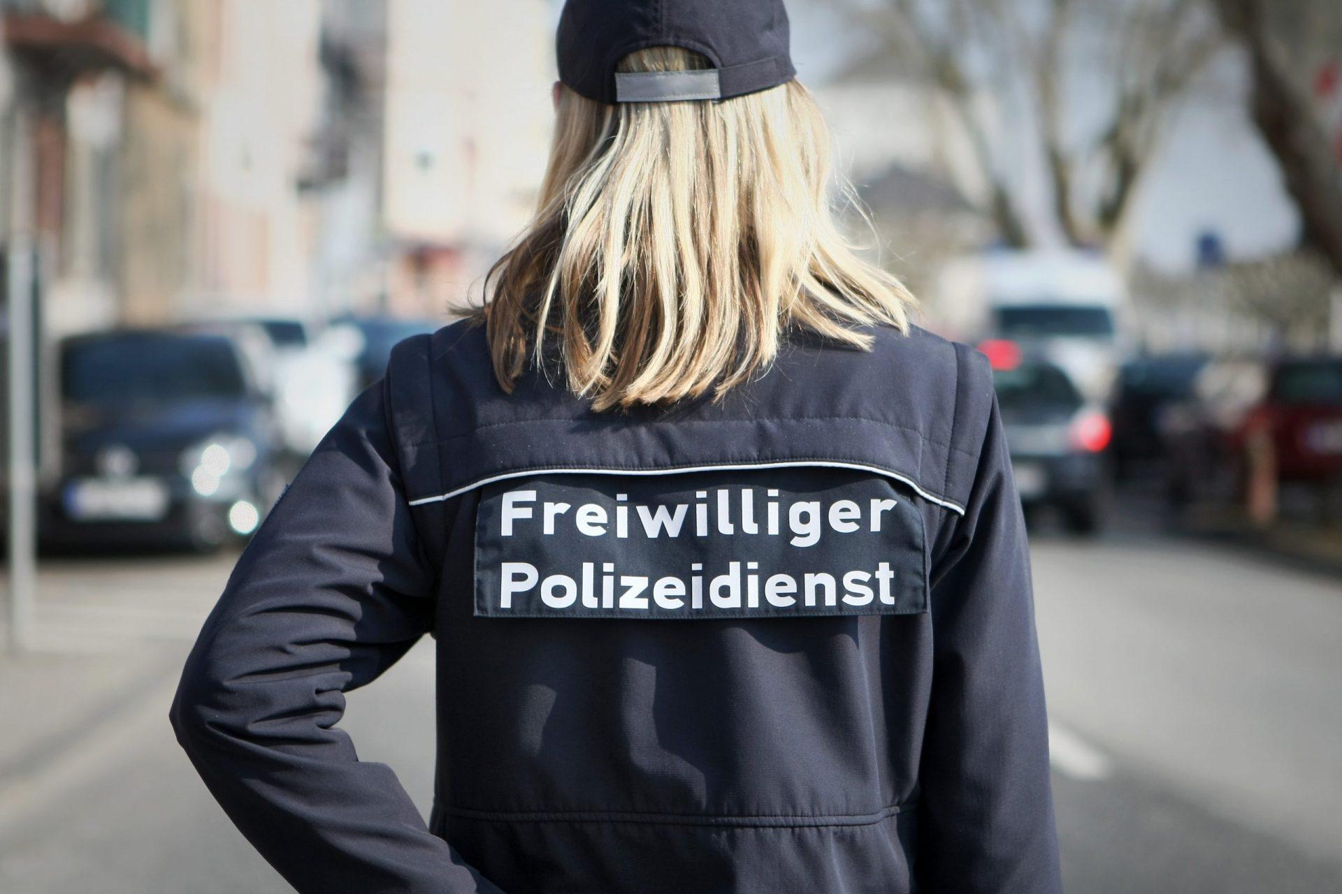 """Eine Frau mit dem Aufdruck auf der Jacke """"Freiwilliger Polizeidienst"""""""