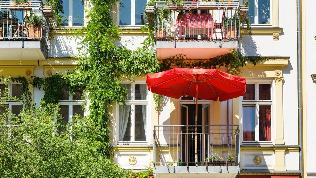 Haus mit Balkon und rotem Sonnenschirm