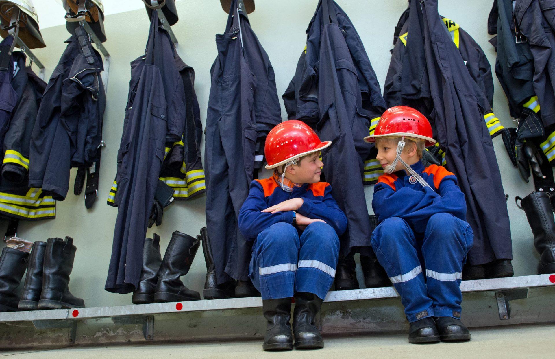 Nachwuchs für die Feuerwehr - zwei Kinder in Feuerwehr-Anzügen sitzen in der Garderobe vor Feuerwehrjacken