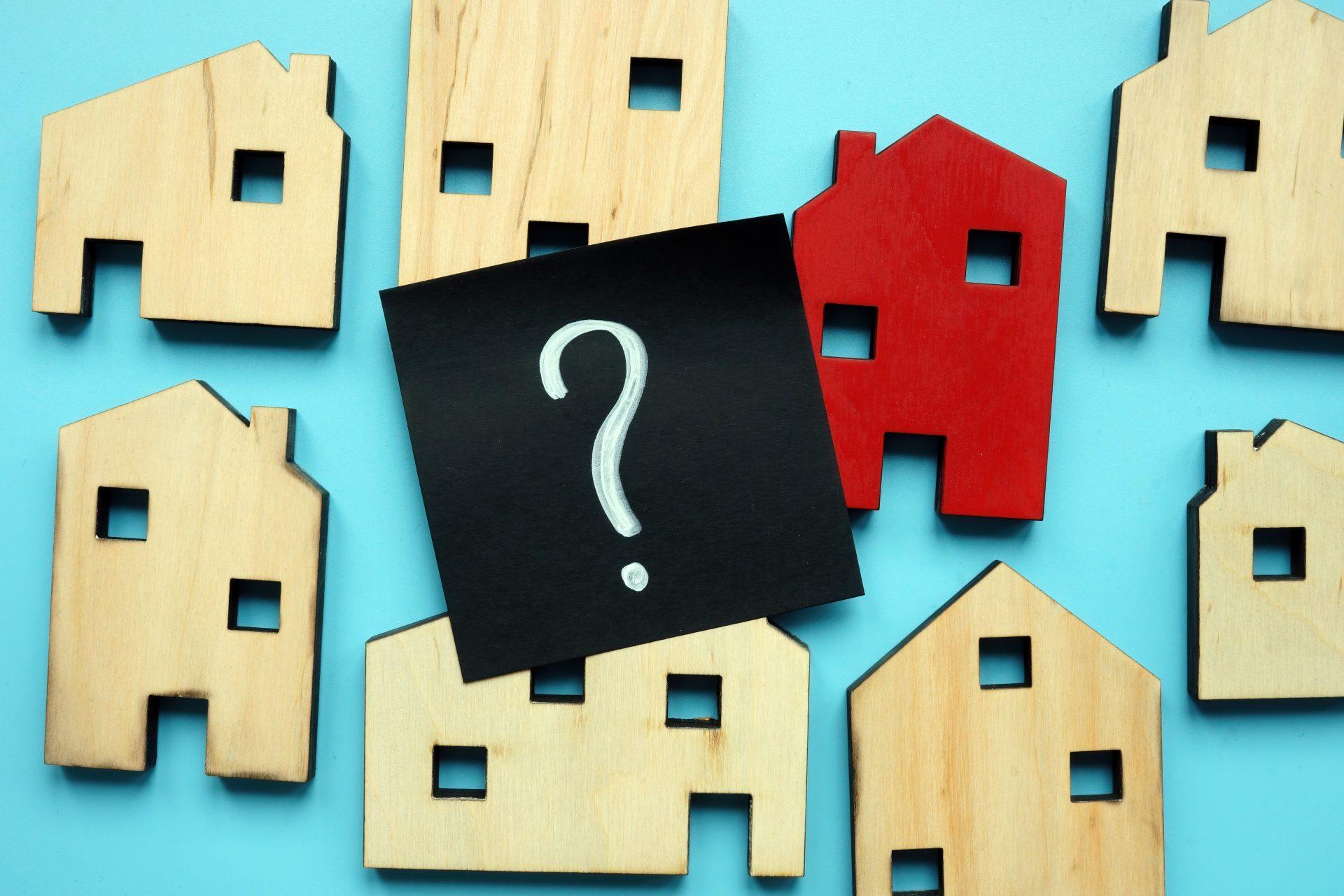 Winzige Häuser aus Holz und Fragezeichen