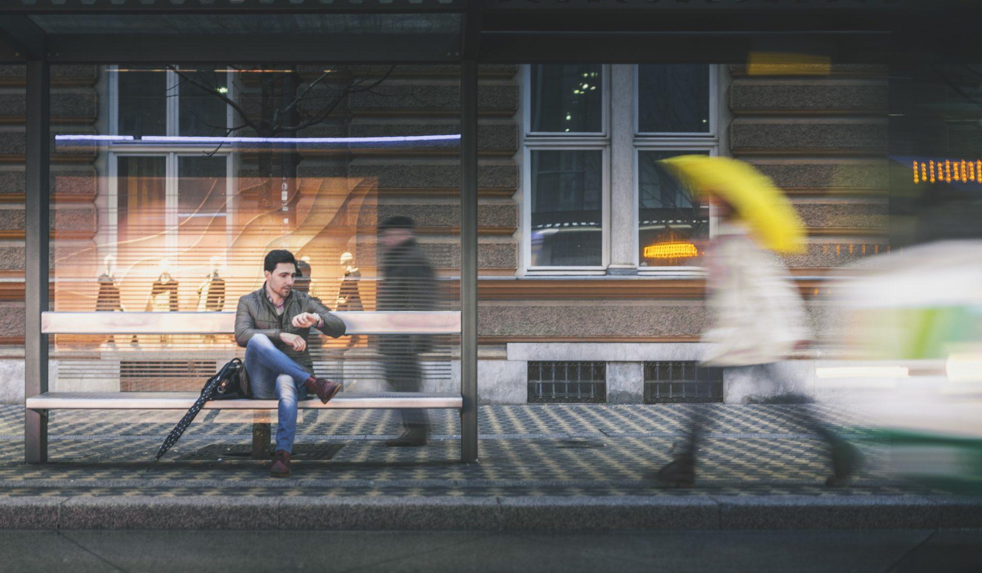 Mann sitzt an der Bushaltestelle an einem regnerischen Abend