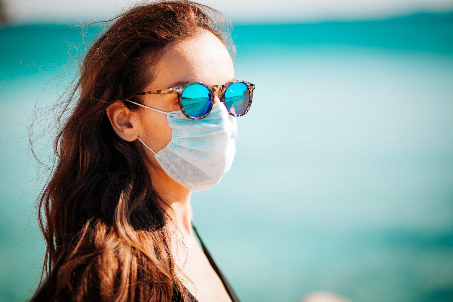 Frau trägt schützende Gesichtsmaske am Strand
