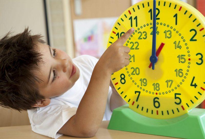 Kleiner Junge zeigt auf eine gelbe Plastik-Uhr