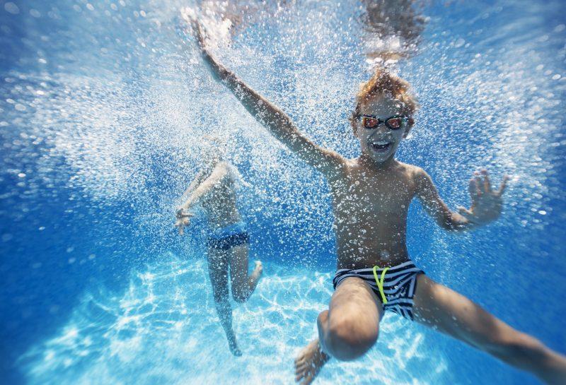 Kinder spielen unter Wasser im Pool