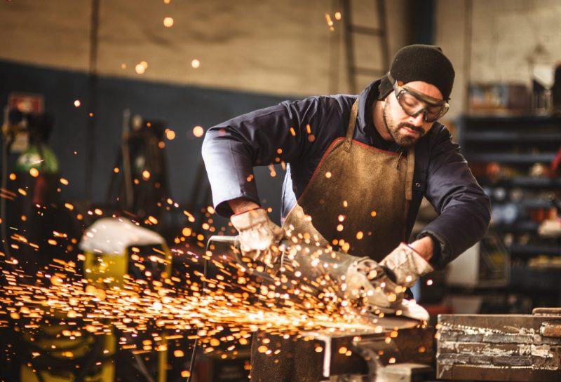 Handwerker arbeitet mit Schleifmaschine
