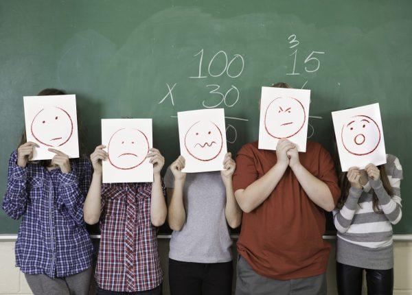 Schüler halten sich Schilder mit aufgemalten Gesichtern vor das Gesicht und stehen vor einer Tafel