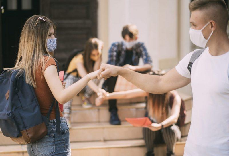 Schüler mit Maske geben sich eine Firstbomb