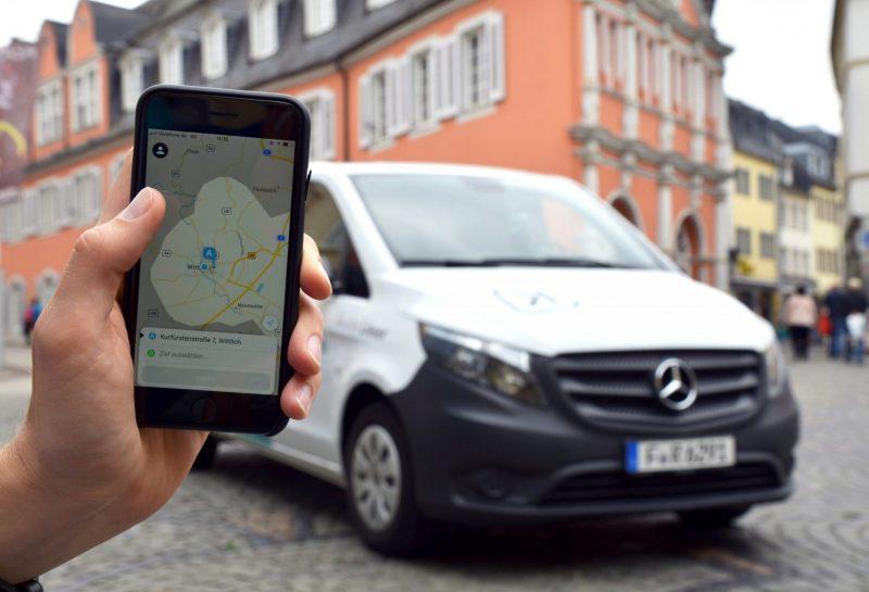 Hand mit Handy und Kleinbus im Hintergrund