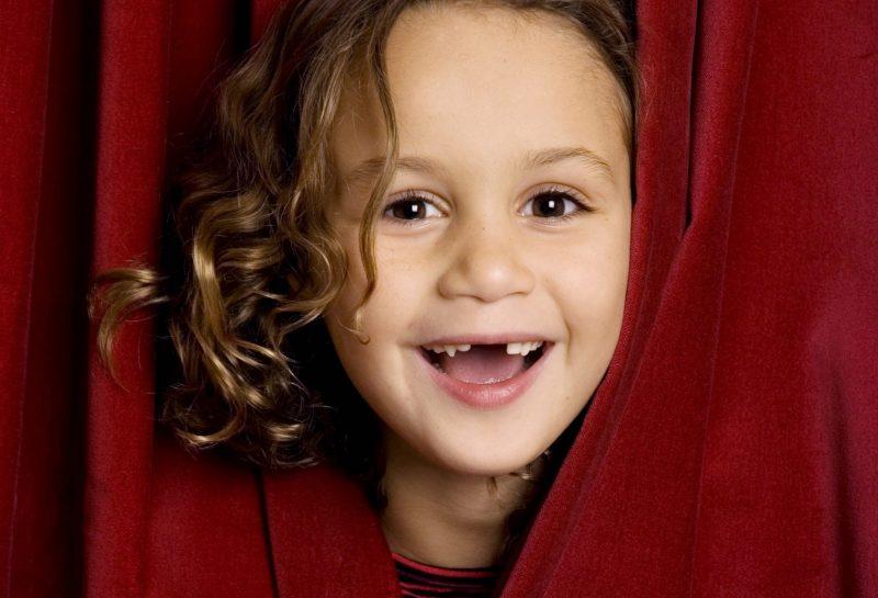 Lachendes Mädchen schaut hinter einem Theatervorhang hervor