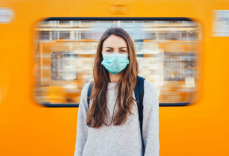 Woman wearing a surgical mask standing in front of the moving train
